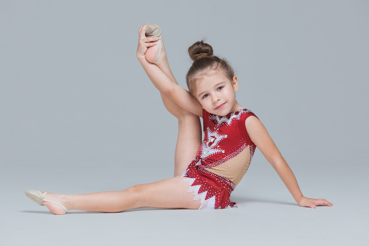 Flexible little girl in beautiful red dress is stretching doing gymnastic exercises on grey background